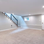 Light grey and spacious basement area with staircase.