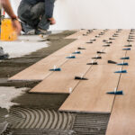 Construction workers laying tile over concrete floor using tile levelers, notched trowels and tile mortar