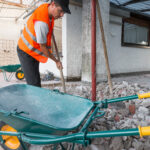 Reconstruction of waterproofing and insulation of a roof - terrace. Phase of excavation and preparation of the fund. Worker removes the rubble