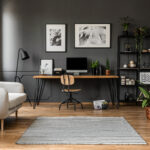 Posters on grey wall above wooden desk with computer monitor in modern workspace interior with plants
