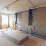 Workers are installing plasterboard (drywall) for gypsum walls in apartment is under construction, remodeling, renovation, extension, restoration and reconstruction.