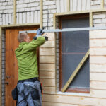 worker restoring old brick house facade with new wooden planks